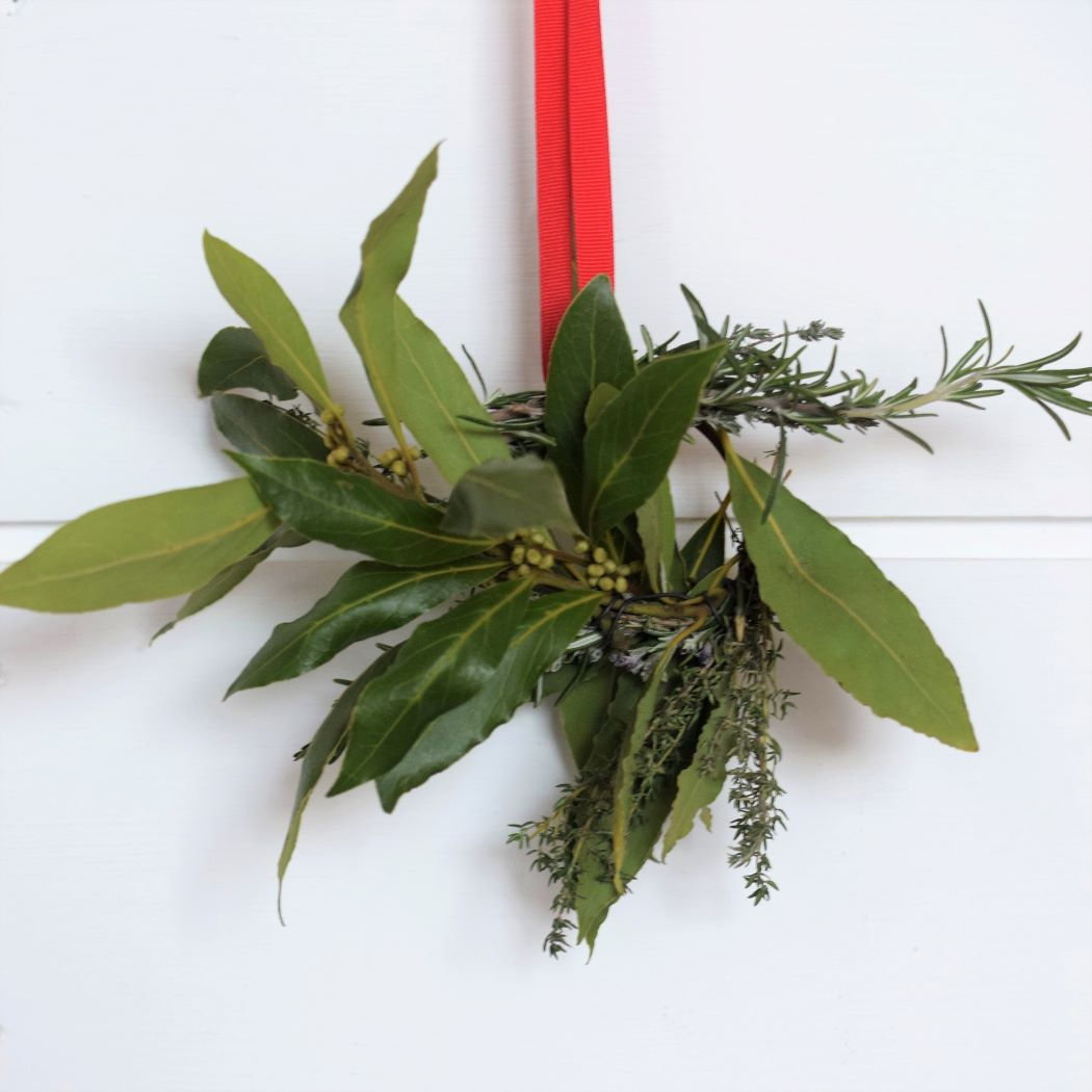 circle of herbs hanging from red ribbon