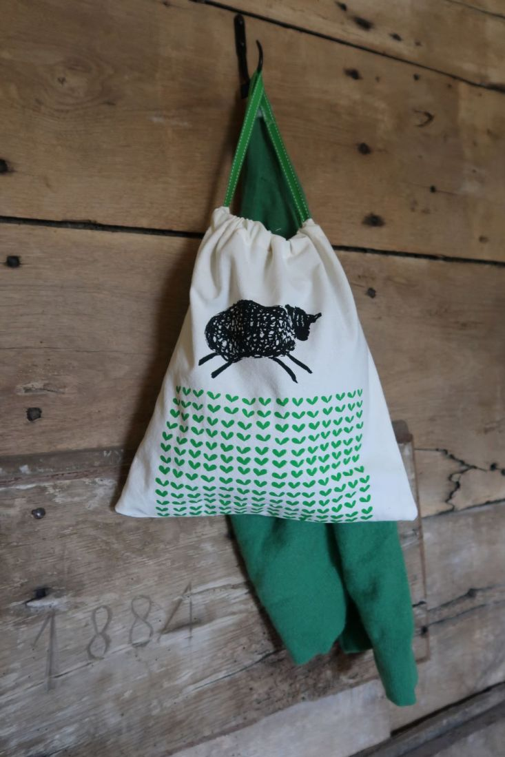 Drawstring bag with print of sheep and field hanging from hook with green cardigan