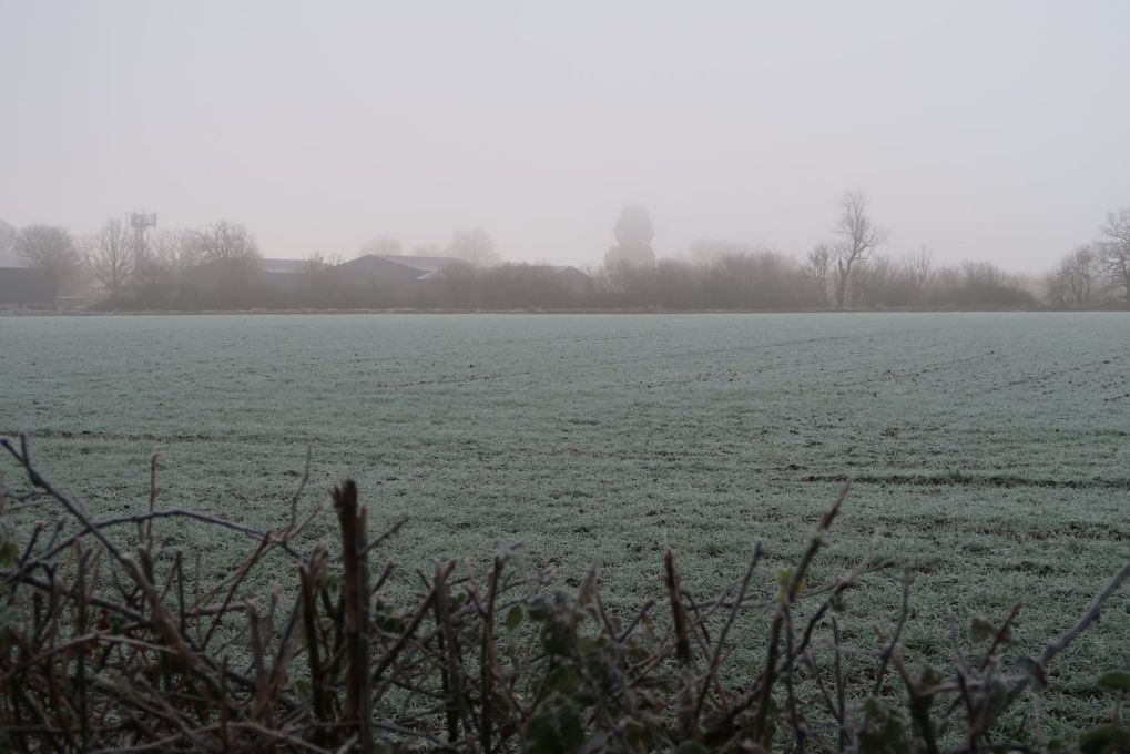 farm in distance on frosty day